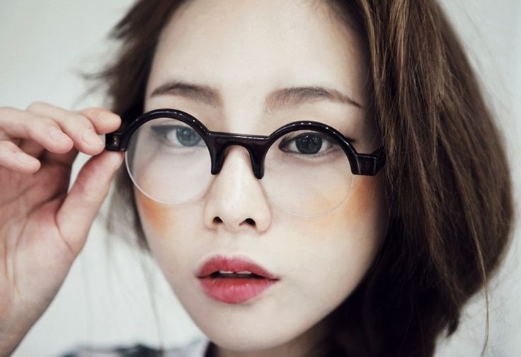 une paire de lunettes rondes à montures noires, un trait d'eye-liner rétro et du fard à joues
