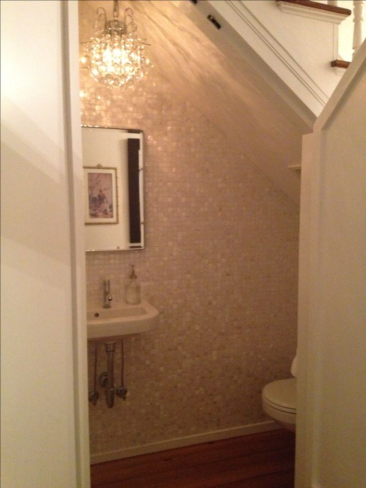 tough to photograph from the hall with the doors on but heres the new tiny bathroom under the stairs with the chandelier in under the stairs bathroom