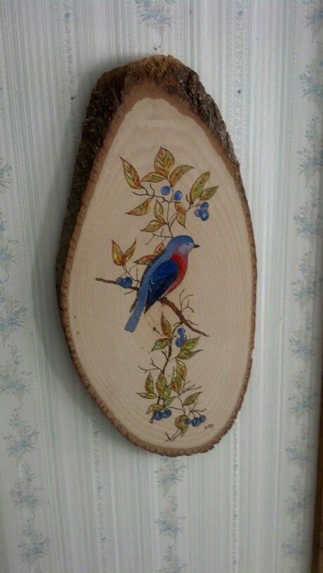 A wood burning I painted over of a blue bird.