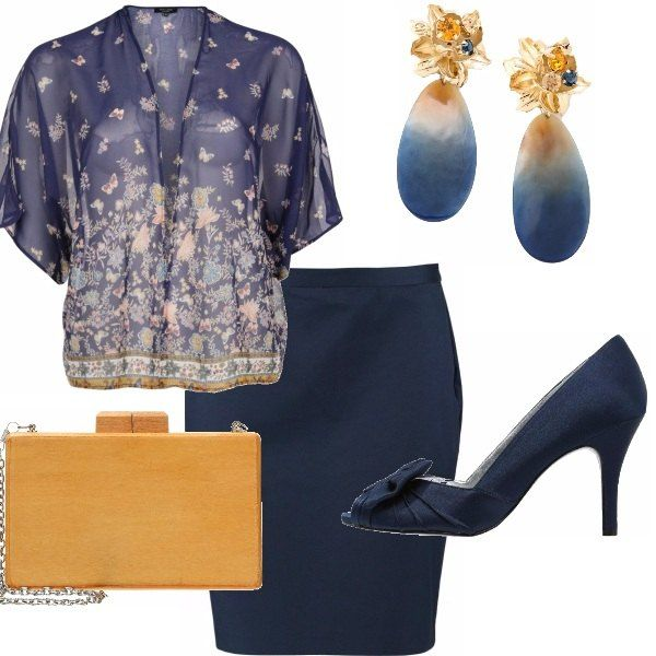 Una curvy elegance: la gonna a matita blu, una blusa con una leggera fantasia che ricorda anche la clutch, le spuntate molto eleganti con fiocco in tinta blu navy. Gli orecchini se piacciono danno un tocco in più, in alternativa delle perle dorate.