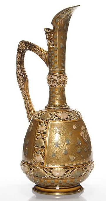 "Zsolnay ewer with pierced & enameled flowers featured on the handle, rim, neck and as a border design. Panels showing raised floral & leaves are set against a busy gold scroll design and the application of bright gold further enhancing the entire vessel. Height 16 1/2 inches. Impressed marked ""Zsolnay Pecs 2287"" also has the company's 5 towers TJM back stamp under the glaze.14/L450U"