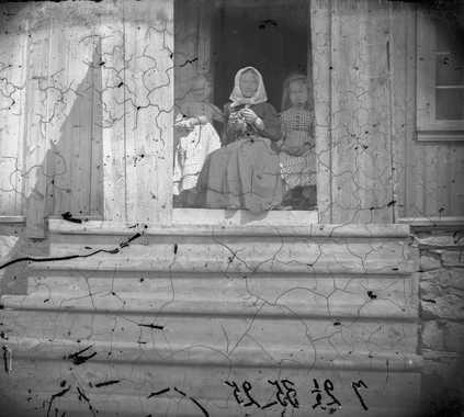 Strikkende kvinne med to barn i døråpning