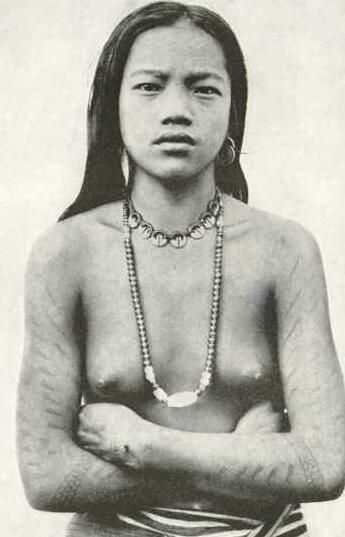 Native Philippine woman with tattoos: a natural beauty, in a proud and defiant stance.