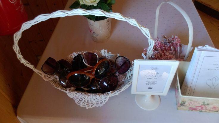 """En korg full med solglasögon i alla möjliga modeller med texten på tavlan bredvid """" Låt inte vår kärlek blända er - låna gärna ett par solglasögon som skydd"""" =)"""