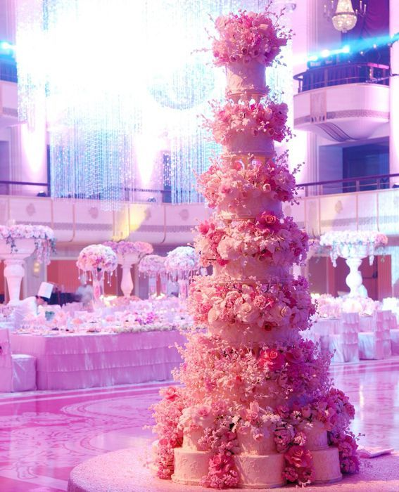 Tall, pink wedding cake adorned with layers tiny sugar flowers.