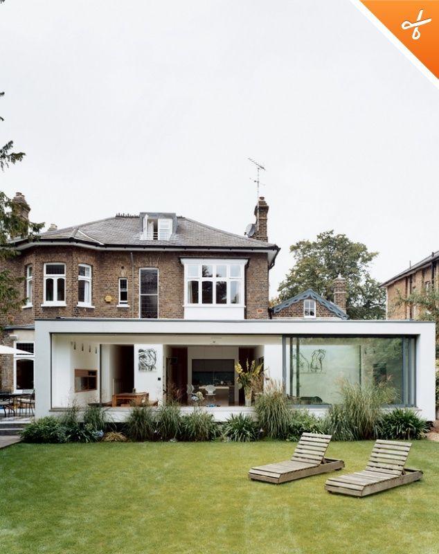White rendered modern extension against brick house
