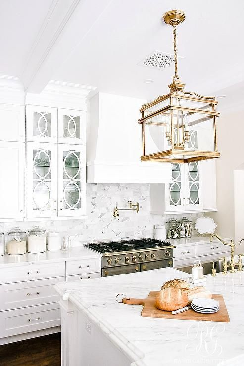 Elegant white kitchen features an stunning Visual Comfort Mykonos 4-Light Lantern hung above a white island topped with a white marble countertop completed with a stainless steel apron sink paired with a polished brass vintage faucet.