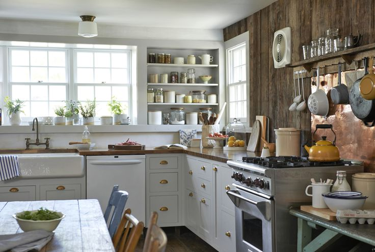 Switching out the stainless steel sink that came with the house for an apron-front porcelain one boosts the room's charm. Brass bin pulls, butcher block countertops, and a copper backsplash behind the range add warmth to the new gray cabinets.   - CountryLiving.com