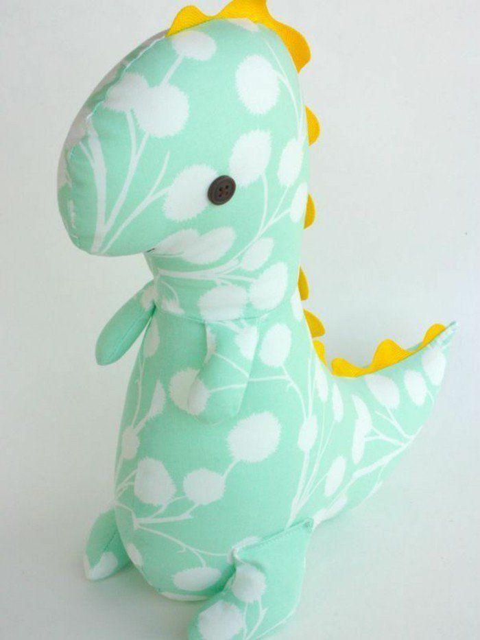 modele de peluche dinosaure, doudou a faire soi meme vert à motifs blancs avec une crête jaune, des boutons noirs comme des yeux