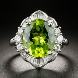 A big bright and luscious faceted oval lime green peridot, weighing 5.18 carats, glistens and glows from within a fanciful platinum frame sparkling north and south with baguette diamonds, and east and west with modern brilliant-cut diamonds. A colorful and cheerful cocktail ring for all seasons. 3/4 inch, .88 carats total diamond weight, currently ring size 5 3/4.