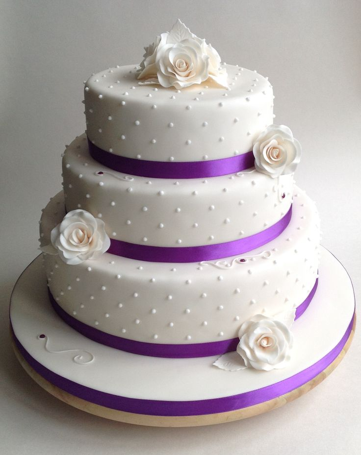 Ivory wedding cake with roses and purple ribbon