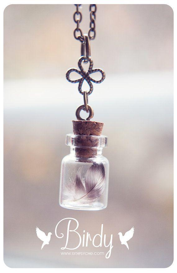 Un collar de botella de vidrio hermosa handmadelittle con una pluma de pájaro natural pequeña y  Las plumas se compran en una granja orgánica libre de