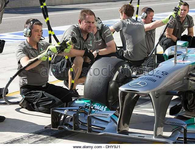 Mercedes AMG Petronas pit crew of driver Nico Rosberg changes tires in pit at practice for F1 United States Grand - Stock Image