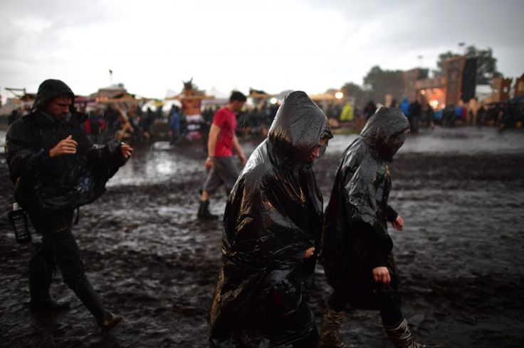 WACKEN, GERMANY - AUGUST 04: Festival goers run from a short but heavy rain shower during the Wacken Open Air festival on August 4, 2016 in Wacken, Germany. Wacken is a village in northern Germany with a population of 1,800 that has hosted the annual festival, which attracts heavy metal fans from around the world, since 1990. (Photo by Alexander Koerner/Getty Images)