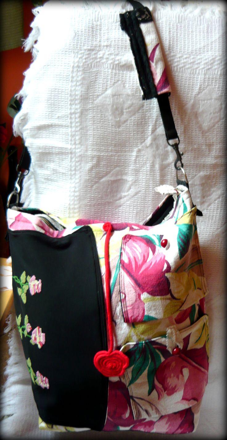 """Nyári virágos táska -Handmade by Judy Majoros: Ez az igazán vidám színösszetételű nyári táska erős vászon anyagból készült. Elején az alapanyagból készült két kis zsebecske -amik gombokkal záródnak-, és fekete díszített pamutból készült nagyobb zseb található.Elejét díszíti még egy piros zsinórból készült """"lógó"""" virágocska. Pántja állítható, vállon, vagy keresztben is hordható. Belsejében egy nagyobb cipzárral záródó, és egy kisebb zseb található."""
