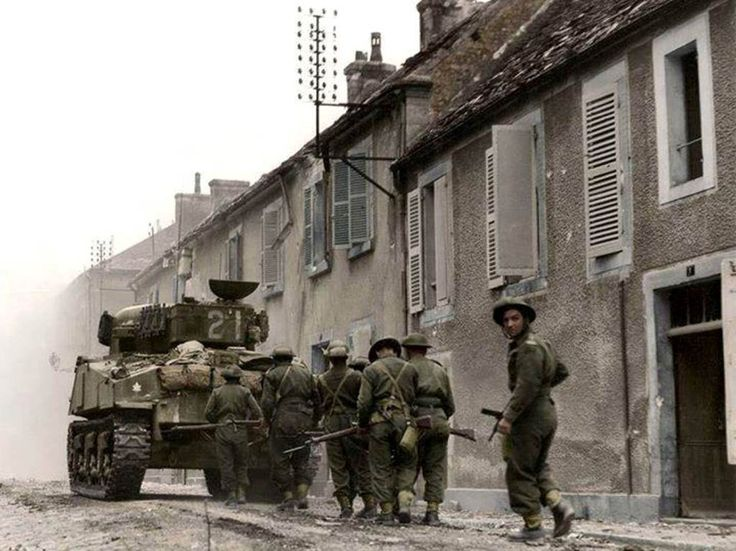 CAF M4A4 Sherman tank No. 21 (possibly 'Bomb') of the Sherbrooke Fusiliers Regt ( 27th Armoured Regt), 2nd Cdn Armd Bde (Independent ) covers soldiers of the Fusiliers Mont-Royal, 2nd Infantry Div in Rue