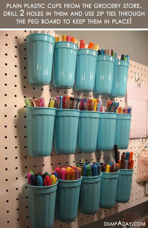 Take plastic cups from the grocery store, drill two holes in the back, and use zip ties to secure them to a peg board! Becomes great storage for art supplies or other nicknacks.  cute, colorful, effective, and cheap!
