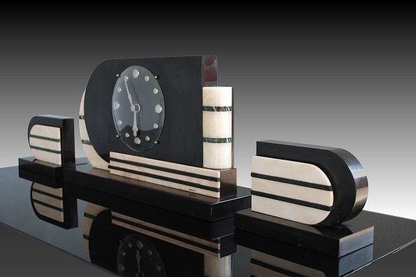 """Streamlined machine age clock. Stunning art deco period marble clock. Great Streamline Machine Age inspiration. French 1930's / 1940's work. Could be attributed to Raymond Loewy famous designer. Clock is made of marble and bronze. Clock itself is 18"""" x 4"""" x 10"""". Each side element (that can be converted in book ends) is 7"""" x 3.5"""" x 5"""". (hva)"""