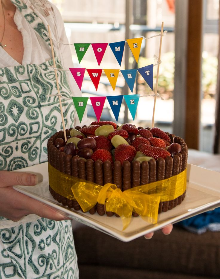 My 'Home Sweet Home' House Warming Celebration Cake - Chocolate fudge cake with classic chocolate butter cream icing, surrounded by chocolate fingers, topped with fresh fruit.  Finished off with a bunting banner and ribbon.