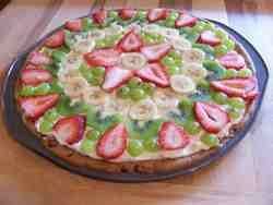 Fruit Pizza  made with chocolate chip cookie dough for the crust and spread with cream cheese. Strawberries, grapes, bananas, and kiwi fruit.