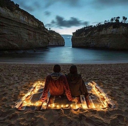 Create a cozy date night beach picnic with a blanket and battery powered fairy lights. #romance