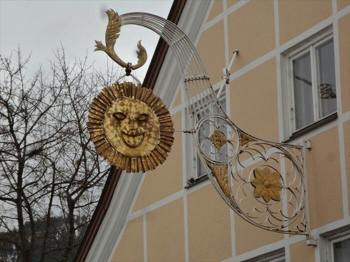 This is an old unique artistic shop sign for a restaurant called 'Gasthof zur Sonne' (Restaurant Sun). It is located in the 'Kemptener Straße' in Nesselwang, Germany, Bayern