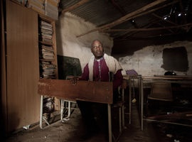 The Archbishop sits in a classroom in the Eastern Cape reflecting