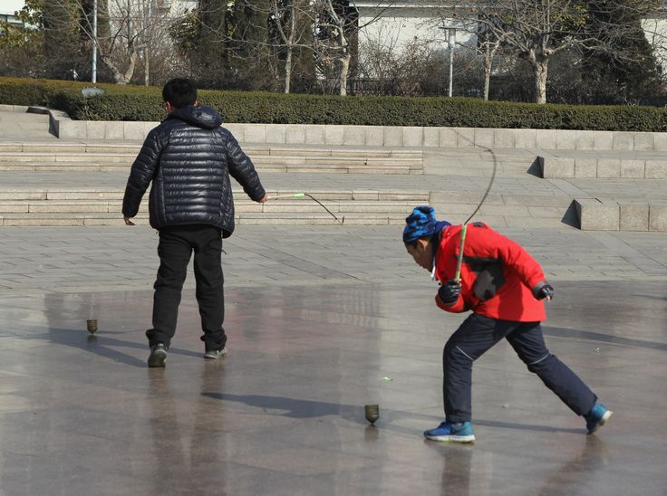 A traditional and popular sport in China, lash the spininning top continuously to keep it moving.