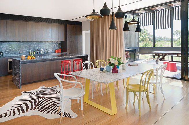 In this Australian home, classic Tom Dixon pendant lamps contrast with a bright dining table setup.