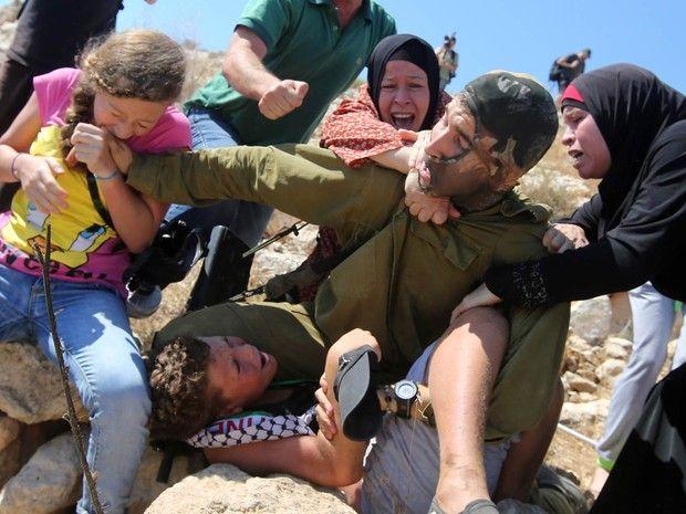 Menina palestina morde a mão de um soldado israelense, que é atacado por mulheres após imobilizar um menino durante confronto na vila de Nabi Saleh, perto de Ramallah, na Cisjordânia. Manifestantes protestavam contra o confisco de terras palestinas (Foto: Abbas Momani/AFP)