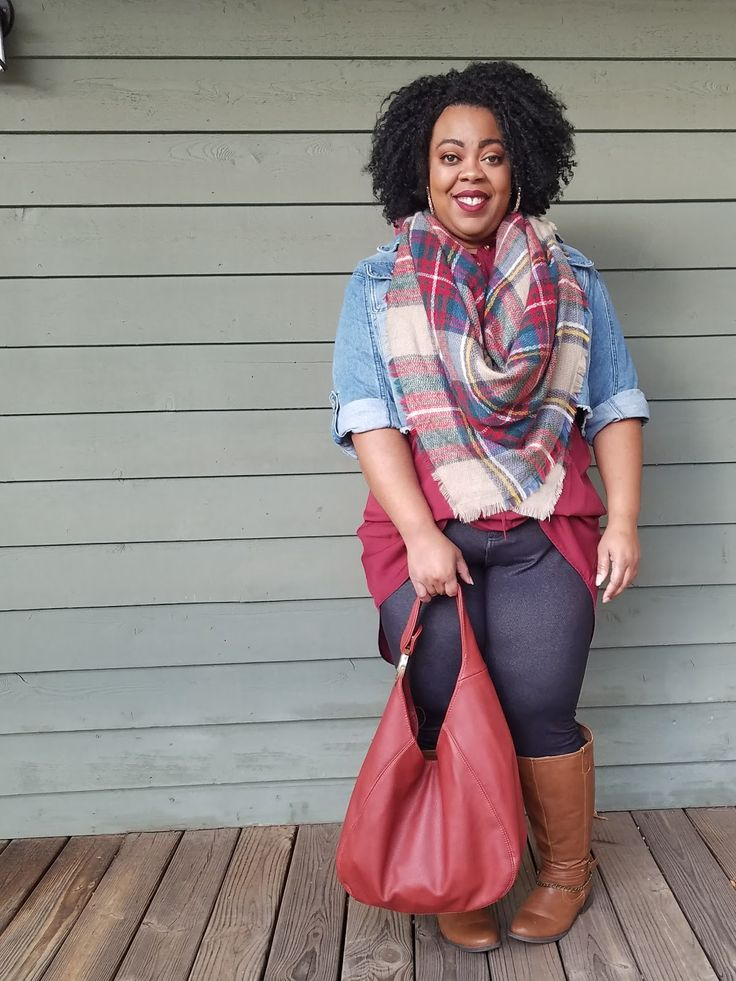 Plus size model in blanket scarf, denim jacket, jeggings and tall boots.