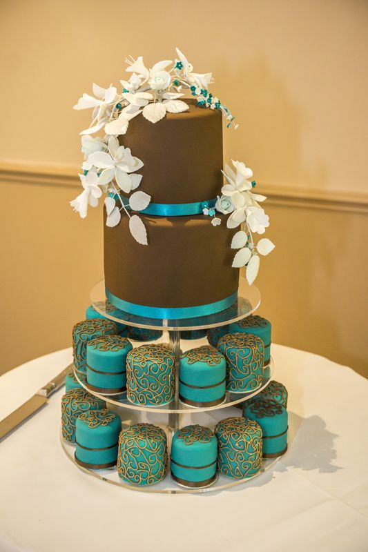 A lovely brown and teal 2 tier cake with colour matching cupcakes.
