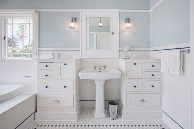 In white with accents of cobalt blue, the new master bath is outfitted with a soaker tub and pedestal sink, a towel warmer, and a separate shower.