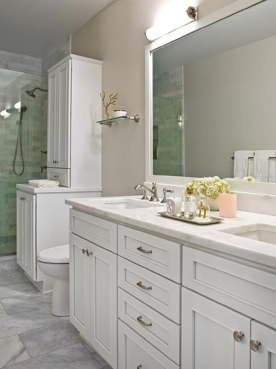 White and beige bathroom features a white dual washstand accented with polished nickel hardware and a white marble countertop fitted with sinks paired with polished nickel faucets fixed in front of a white marble backsplash located beneath a white framed full length vanity mirror.