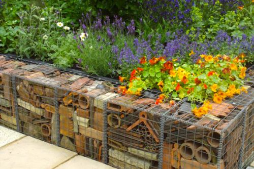 Love this idea of gabion walls made of old scrap metal and other recycled parts.