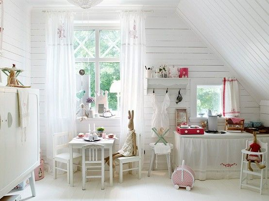 White wood floors, white wood walls and white wood furniture works perfectly with hits of pink and red.