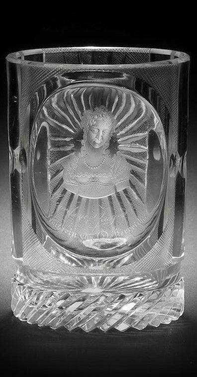 A Bohemian engraved Royal beaker by August Böhm senior, circa 1830-1835 The cylindrical form with two square panels, one containing an oval medallion cut in high relief, decorated with a titled portrait inscribed Caroline Auguste, Kaiserin von Oesterreich, the other cut with a viewing lens and a sunburst pattern surrounded by mitre diamonds, each of the sides with three pillar flutes cut with single lenses, the base with diagonal prismatic flutes and a star-cut underside, 12.7cm high (slight…