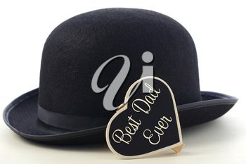 Fathers Day concept with mens black bowler hat and Best Dad Ever blackboard greeting on a white wood table.