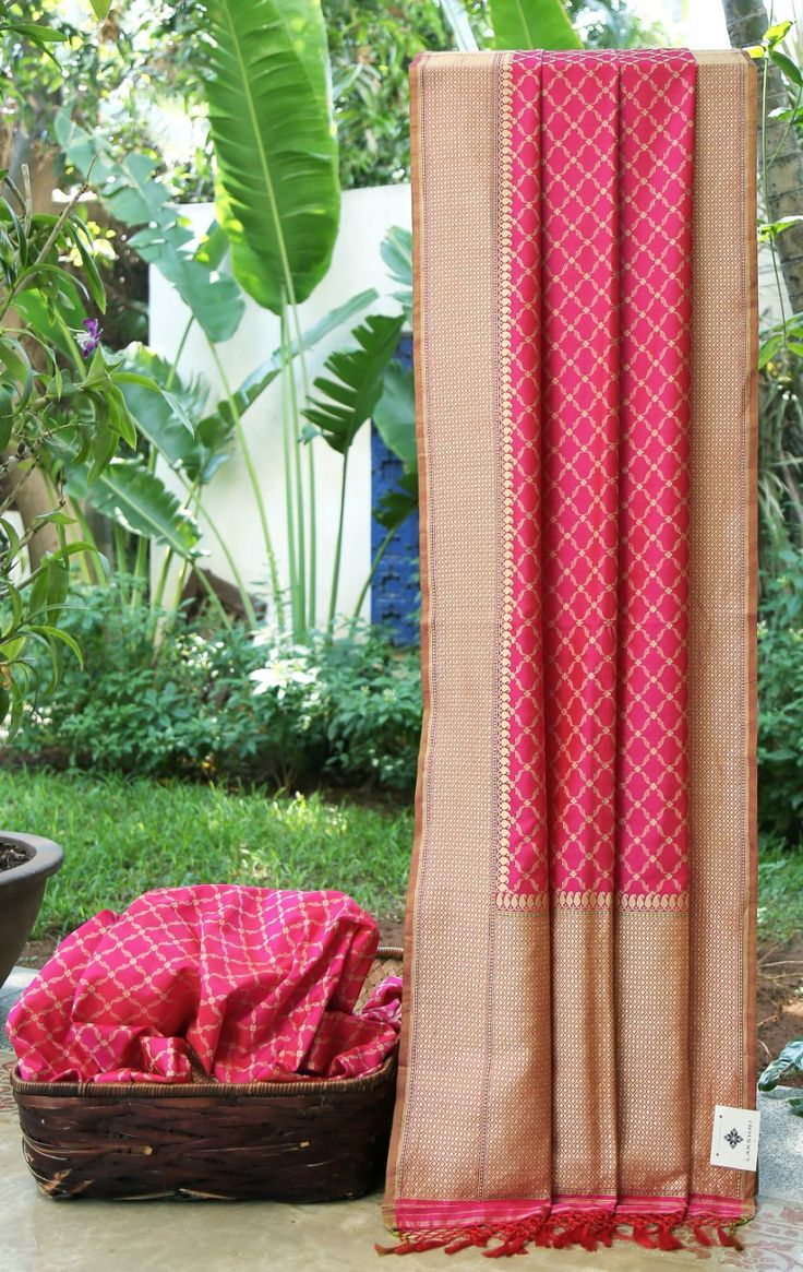 This hot pink Benares silk has a pattern of diamonds all over in gold zari and beige thread work. The border and pallu have intricate gold zari work with a hint of green making it a much desirable …