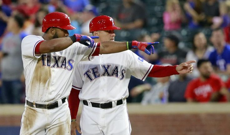 Texas Rangers shortstop Elvis Andrus (left), who had three hits, and first base coach Hector Ortiz point to the dugout after Elvis singled in Mitch Moreland in the third inning against the New York Yankees at Globe Life Park in Arlington, Tuesday, April 26, 2016. (Tom Fox/The Dallas Morning News)