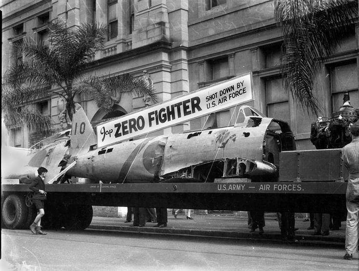 Remains of a Japanese Zero exhibited in an Air Training Corps march through Brisbane streets, 31 July 1943. The march was designed to stimulate the drive for Air Training Corps recruits. 'Remains of a Zero exhibited in yesterday's Air Training Corps march are all that was left of Jap machine shot out of northern skies...' (Information taken from: Sunday truth, 1 August 1943). (Description supplied with photograph)