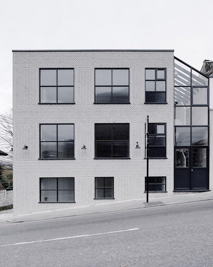 Pale grey herringbone brick exterior, black steel-frame windows, atrium, sloping block