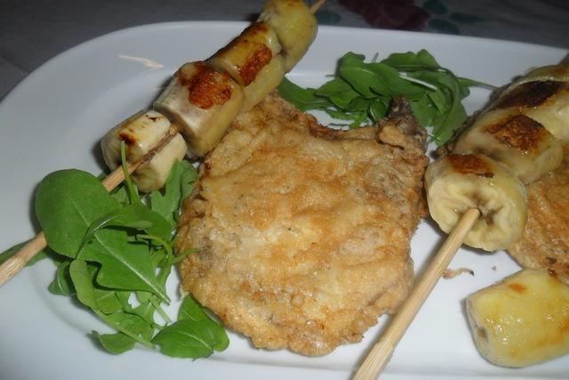 Costeleta de cerdo rebozada con brocheta de plátano. Ver la receta http://www.mis-recetas.org/recetas/show/38545-costeleta-de-cerdo-rebozada-con-brocheta-de-platano