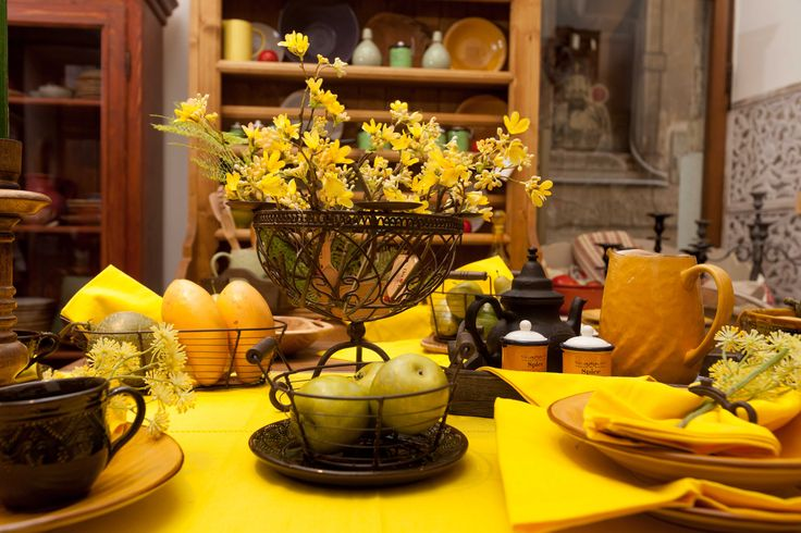 Forsythia flowers burning powerfully from the goblet lighting up the whole place. Chaotic lines form vases, cups and ripen fruits.