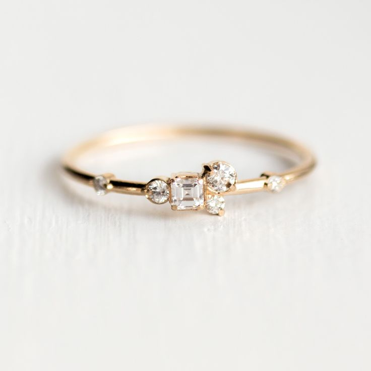 This simple and sweet 14k yellow gold piece features a cluster of sparkly sugar-like white diamonds, set in prongs. Gemstones: One 2.6mm asscher cut white diamond (VS clarity, G-H color) One 2.4mm whi