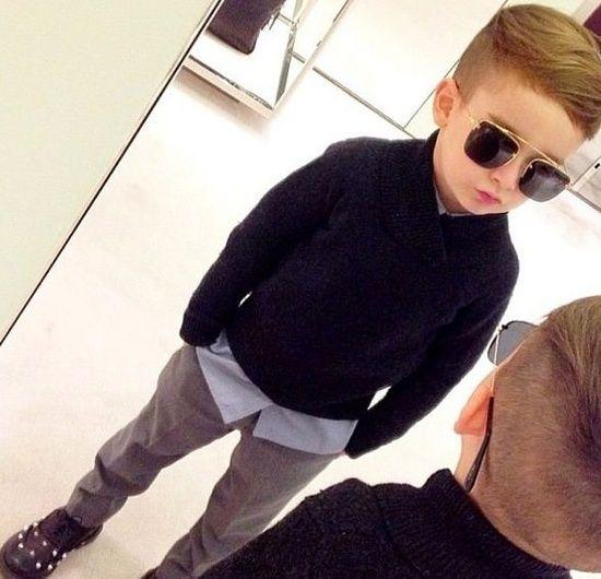 El chico lleva el camisa negra, los pantelones grises, y los lentes cafés.