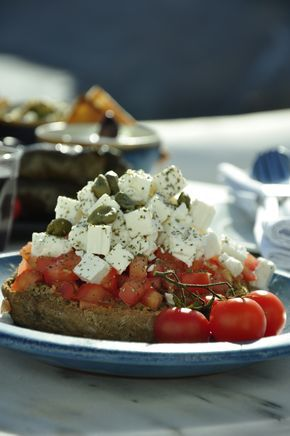 Dakos is a Cretan dish consisting of a slice of soaked dried bread or barley rusk (paximadi) topped with chopped tomatoes and crumbled feta or mizithra cheese, olives and flavored with herbs such as dried oregano