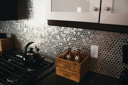 Brushed stainless steel penny round tiles as backsplash, via Floorology.