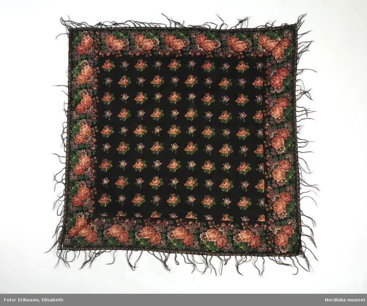 Kvadratiskt halskläde i bomullskypert med blocktryckt mönster s.k kattuntryck. Svart botten, i mittspegeln strödda rosenkvistar och lila blomknoppar, kantbård med snedställda blombuketter med bulliga rosor och mindre lila och rosa blommor.  Invikta kanter med iknuten gles frans av svart ullgarn.  I mycket gott skick.  Enligt uppgift ett brudkläde från 1840. Jfr.  halskläde 130.215 från Nås i Dalarna, som är mycket snarlikt men något mindre i formatet.  /Berit Eldvik 2012-01-26