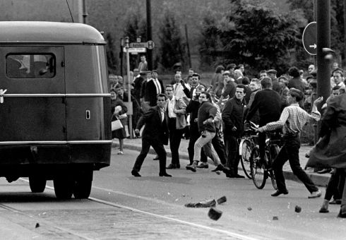 Berlin, 1962: West Berliners on the sidewalk near Checkpoint Charlie throw rocks at a military bus carrying Soviet troops across the border to the Soviet war memorial a few months after the construction of the Berlin Wall